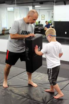 Young Everett Martin strikes a bag held by Strike Back Martial Arts owner Dave Nicchitta at a Strike Fitness class for children with Down syndrome.