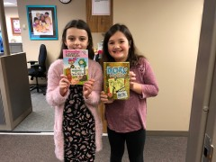 Third graders Ella and Julianna hold up two of the books from the donation.
