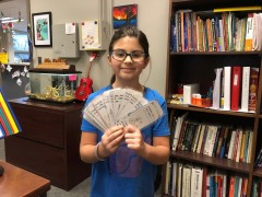 Third grader Sofia holds up bookmarks that she and her classmates made for the children at the YWCA.